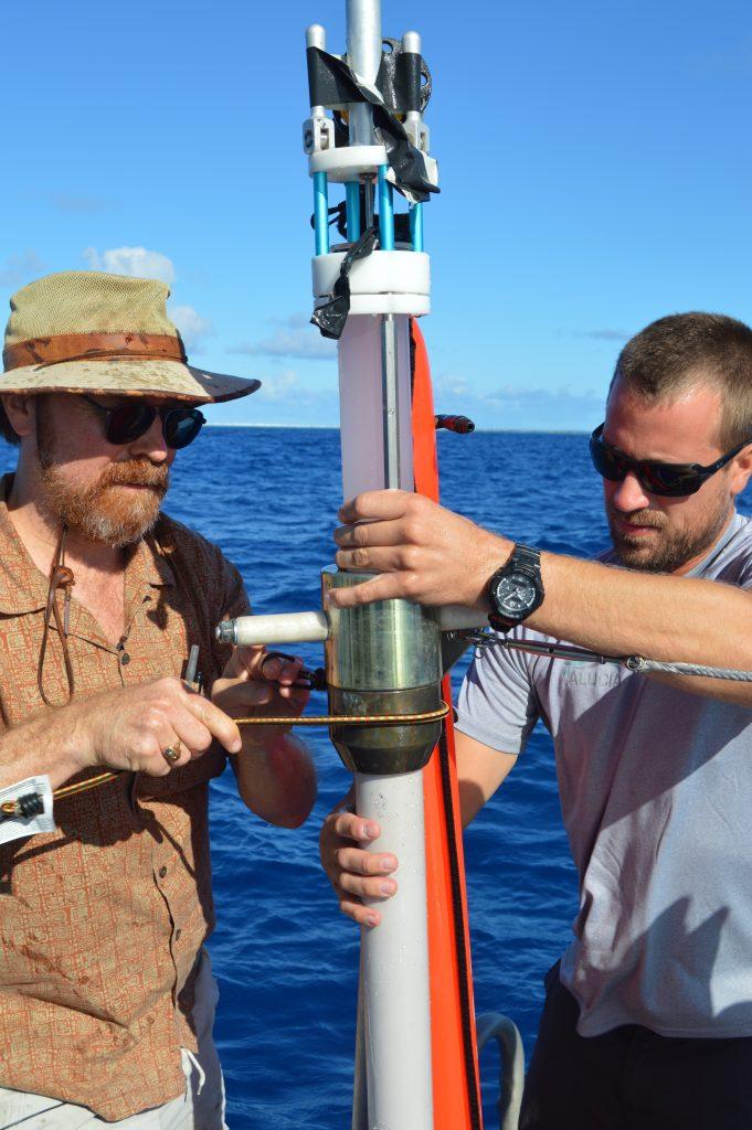 Ken Buesseler and a crew member assembling the sediment coring device.